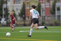 Mädchenfußballspieler nach der Kugel stockfotografie