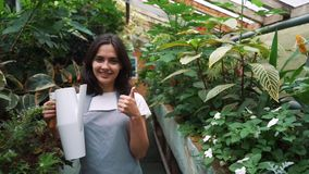 Mädchengärtner betrachtet die Kamera und das Lächeln und hält eine Gießkanne nach Bewässerungsblumen stock video footage
