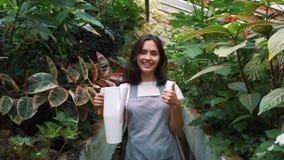 Mädchengärtner betrachtet die Kamera und das Lächeln und hält eine Gießkanne nach Bewässerungsblumen stock video