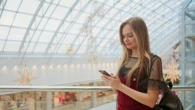 Mädchengebrauchshandy, Unschärfebild innerhalb des Malls als Hintergrund stock video