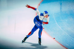Mädchengeschwindigkeitsschlittschuhläufer lässt eine Drehung auf Eis laufen Stockfotografie