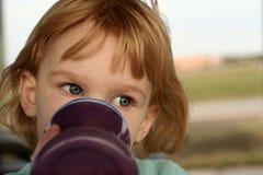 Mädchengetränke vom sippy Cup stockfotografie