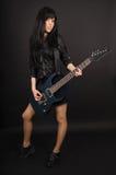 Mädchengitarrist mit seiner Gitarre auf einem schwarzen Hintergrund Stockfoto