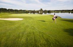 Mädchengolfspieler, der auf Golfplatz mit Golfbeutel geht. Stockfoto
