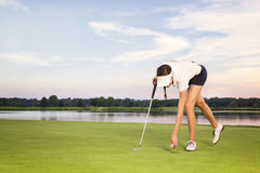 Mädchengolfspieler, der Kugel vom Cup aufhebt. Lizenzfreies Stockbild