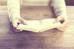 Mädchenhände, die ein offenes Buch führen Stockbild