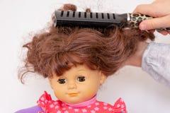 Mädchenhände, die Haar der weiblichen Puppe kämmen stockbild