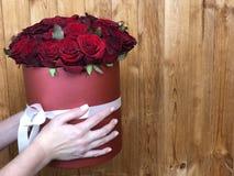 Mädchenhände halten einen herrlichen Blumenstrauß von roten Rosen lizenzfreie stockbilder