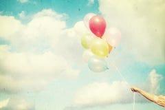 Mädchenhand, die mehrfarbige Ballone hält Lizenzfreies Stockfoto