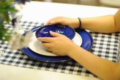 Mädchenhand, die Platten auf Tabelle anhält Lizenzfreies Stockfoto