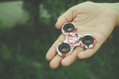 Mädchenhand hält und zeigt Handunruhe-Spinnerspielzeug stockfoto