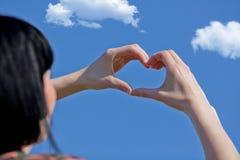 Mädchenhand im blauen Himmel der Herzformliebe Lizenzfreie Stockbilder