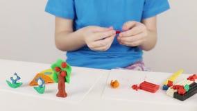 Mädchenhandformteilhaus, Baum, Blumen vom Plasticine auf Tabelle im Raum stock video