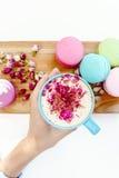 Mädchenhandgriff ein blaue Schale Morgenaromacappuccino Französische macarons und Rosenblumenblätter auf hölzernem Schreibtisch Stockfotografie