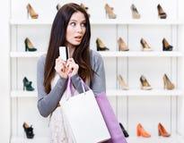 Mädchenhandkreditkarte im Schuheshop Stockfoto