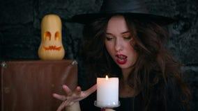 Mädchenhexe auf Halloween auf a, brennende Kerze und Casting halten ein Bann Jack-O-Laterne stock footage