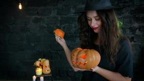 Mädchenhexe auf Halloween auf a, Kürbis mit einer brennenden Kerze und einem Casting halten ein Bann Jack-O-Laterne stock video footage