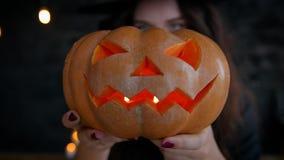 Mädchenhexe auf Halloween auf a, Kürbis mit einer brennenden Kerze und einem Casting halten ein Bann Jack-O-Laterne stock video