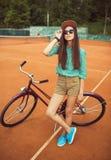 Mädchenhippie, der mit magentarotem Fahrrad auf dem Tennisplatz steht Lizenzfreie Stockfotos