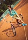Mädchenhippie, der mit magentarotem Fahrrad auf dem Tennisplatz steht Lizenzfreie Stockbilder