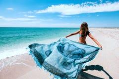 Mädchenholding pareo auf dem Strand stockbild