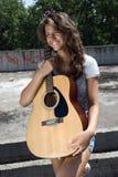 Mädchenholdinggitarre, lächelnd Stockfotografie