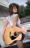 Mädchenholdinggitarre und Betrachten der Kamera Stockfoto