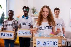 Mädchenholdingkasten mit Plastik, nachdem Abfall mit Freunden sortiert worden ist lizenzfreie stockfotos