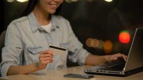 Mädchenholdingkreditkarte und -einkaufen auf Laptop, on-line-Ablagerung, Geschäft stock footage