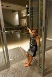 Mädchenholdingoffene Glastür Stockfotos