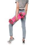 Mädchenholdingskateboard und -aufstellung lokalisiert auf Weiß Stockfotos