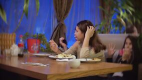 Mädchenjugendlicher, den schlechtes apetite Krisenalter nicht Salat essen möchte, sitzt in einem Café in der Firma der Freundzeit stock footage