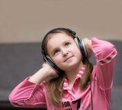 Mädchenjugendlicher, der Musik mit großen Kopfhörern hört und oben nachdenklich schaut Stockfoto