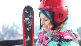 Mädchenjugendlicher in einem Sturzhelm und mit Skis klettert einen Berg in der Skiaufzugkabine Skiort, Familienskifahren stock video footage
