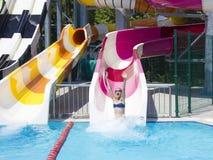 Mädchenjugendlicher im aquapark geht von den Wasserrutschen unten lizenzfreies stockbild