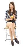 Mädchenjugendlicher, kaukasischer Auftritt, Brunette, ein kariertes Hemd und kurzen Denimkurzen hosen tragend und halten ein Glas  Stockbilder