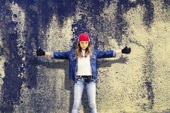 Mädchenjugendlicher mit den weit getrennthänden Denimkleidung Baseballmütze Vor dem hintergrund der alten Betonmauer beschreibung Lizenzfreies Stockbild