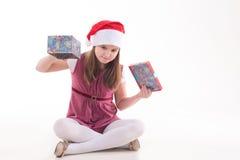 Mädchenjugendlicher mit einem Geschenk in einem Sankt-Hut Lizenzfreie Stockbilder