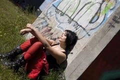 Mädchenjugendlicher mit Fluglage mit Graffiti im b Stockfoto