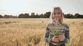 Mädchenjugendlicher mit sechzehn Jährigen mit Blumen von den Kornblumen, die auf einem Weizengebiet aufwerfen stock footage