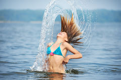 Mädchenjugendlicher mit spritzt vom Haar auf See Stockfotos