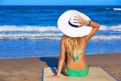 Mädchenjunge, die das Meer mit Strandhut betrachtend sitzen Stockbild