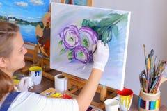 Mädchenkünstler sitzt mit zurück zu Kamera und zeichnet Ölbild mit Stockbilder