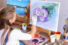 Mädchenkünstler sitzt mit zurück zu Kamera und zeichnet Ölbild mit Stockfotografie