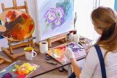 Mädchenkünstler sitzt mit zurück zu Kamera und zeichnet Ölbild mit Lizenzfreies Stockfoto