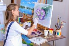Mädchenkünstler sitzt mit zurück zu Kamera und zeichnet Ölbild mit Lizenzfreie Stockfotos