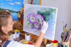 Mädchenkünstler sitzt mit zurück zu Kamera und zeichnet Ölbild mit Stockbild