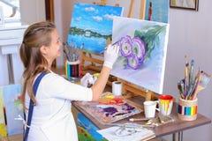 Mädchenkünstler sitzt mit zurück zu Kamera und zeichnet Ölbild mit Lizenzfreies Stockbild