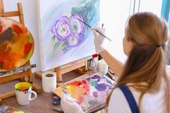 Mädchenkünstler sitzt mit zurück zu Kamera und zeichnet Ölbild mit Lizenzfreie Stockfotografie