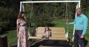 Mädchenkind auf einem Schwingen mit ihren Eltern stock video footage